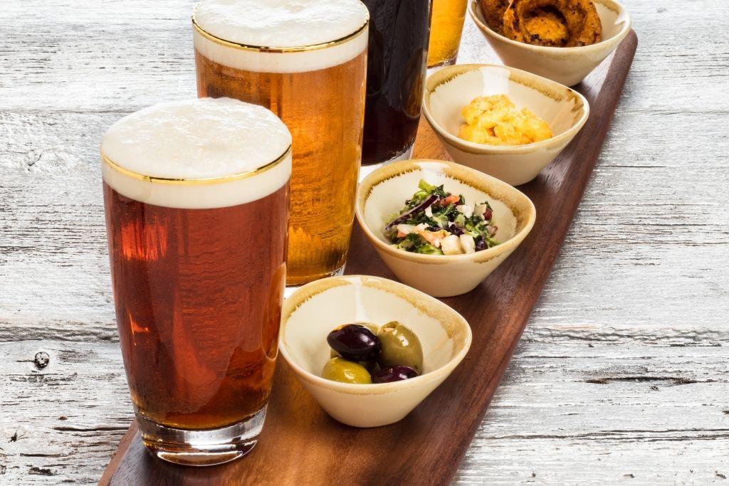 A selection of four beers with small bowls of snacks on the side that all sit stop a wooden table.