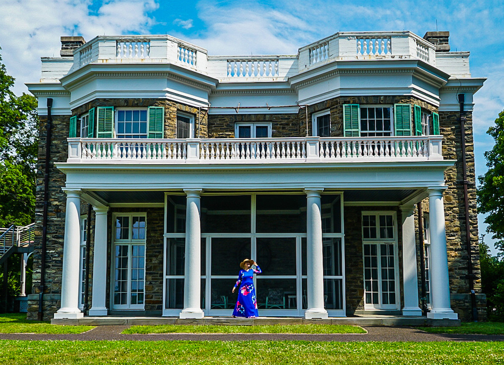 Girl in a blue dress standing in front of the FDR home in Hyde Park, NY.