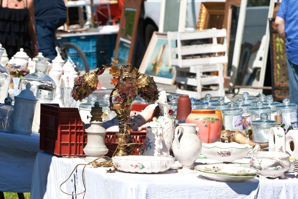 Used items for sale on the table of a flea market.