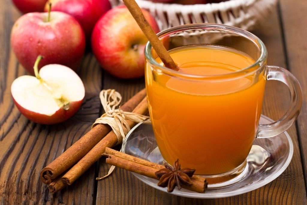 A glass of hot apple cider on a picnic table with cinnamon and freshly cut apples around it.