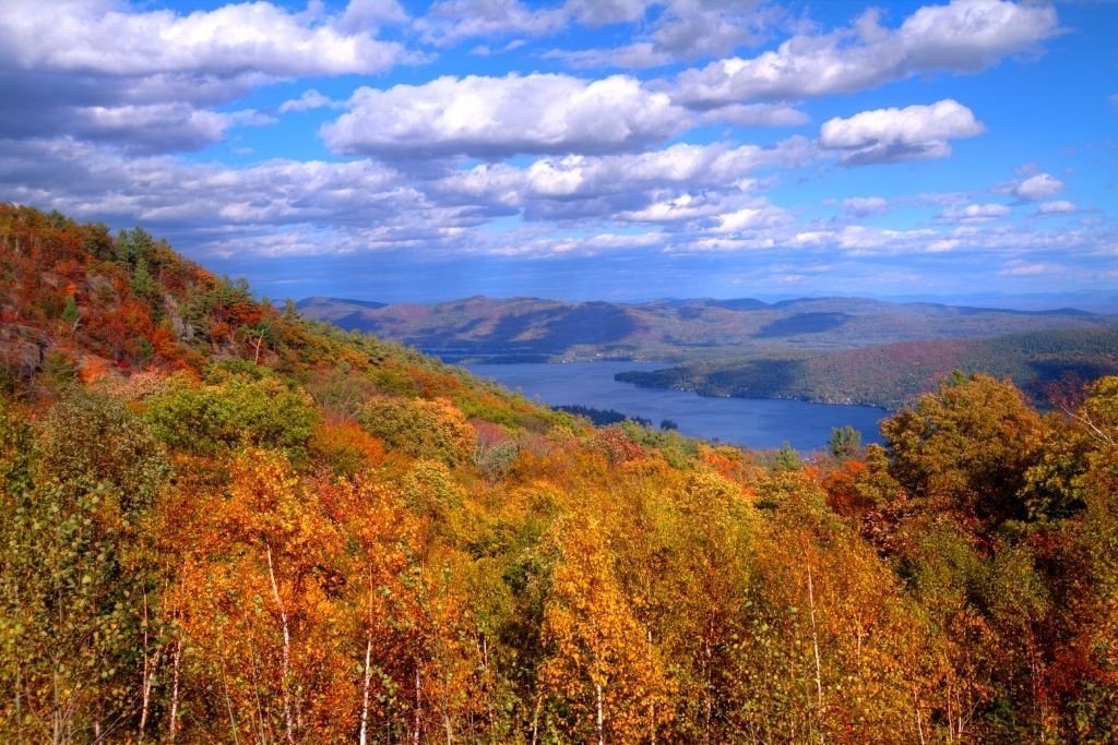 Aerial view of Lake George from the top of a mountain in the fall with vibrant foliage in the foreground.
