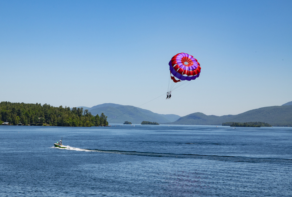 View of Lake George and mountains with two parasailing persons in the foreground.