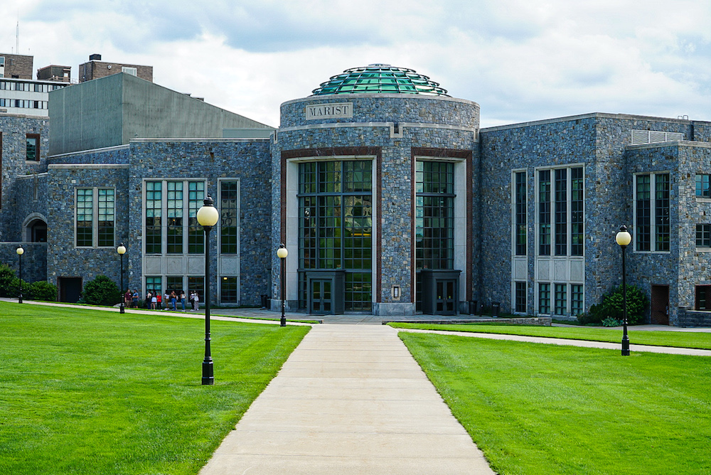 The stone main entrance building of Marist College with lush green grassy fields all around it.