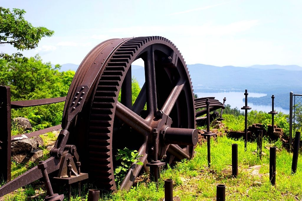An old railway gear at the summit of Prospect Mountain with Lake George in the background.