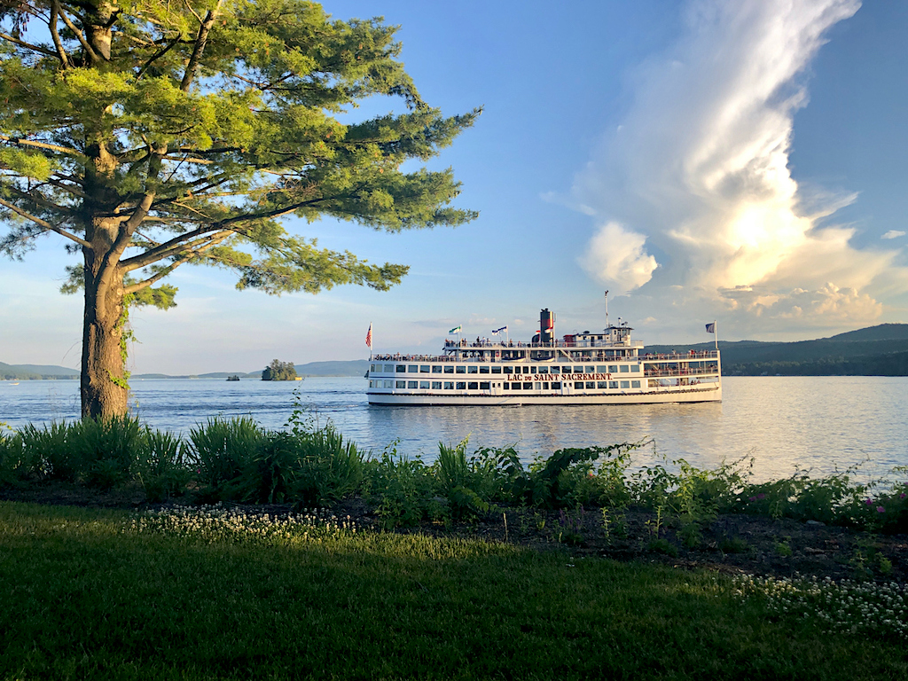 A steamboat sailing across Lake George at sunset