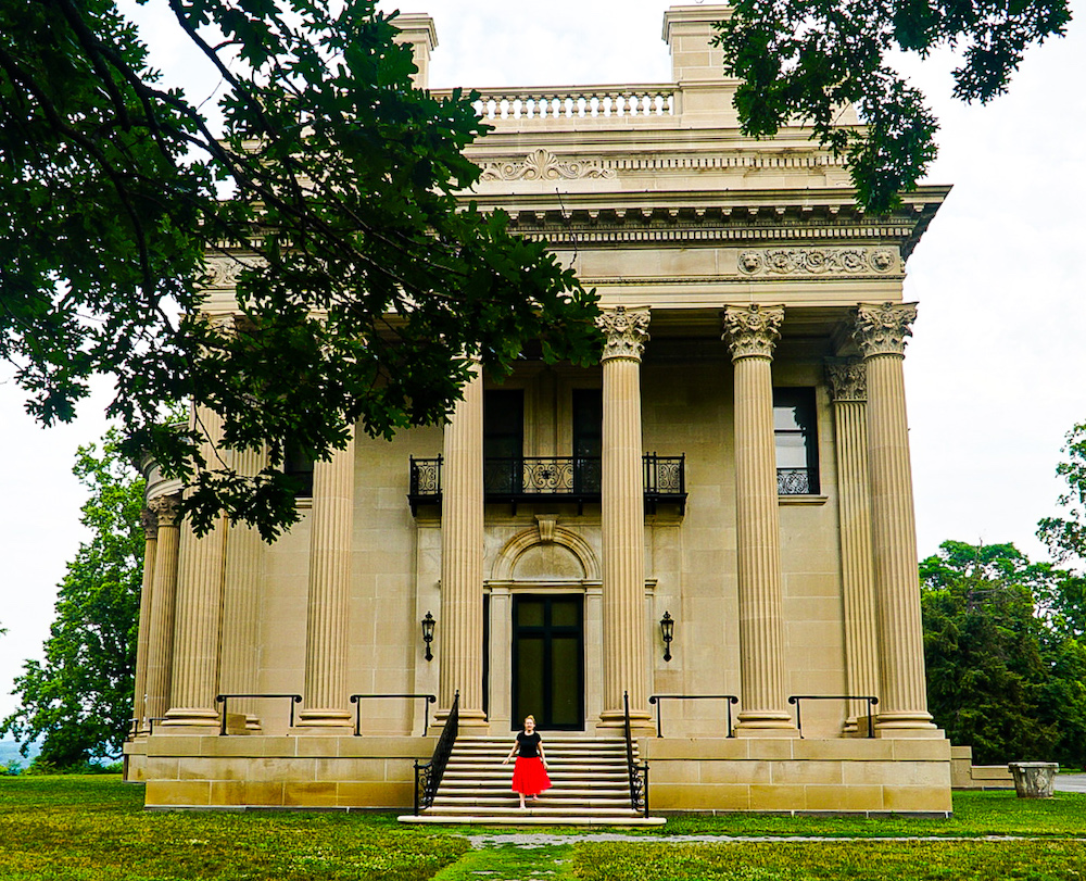 Girl in a red skirt and black shirt standing on the stairs along the exterior of the Vanderbilt Mansion, one of the best things to do in Poughkeepsie NY