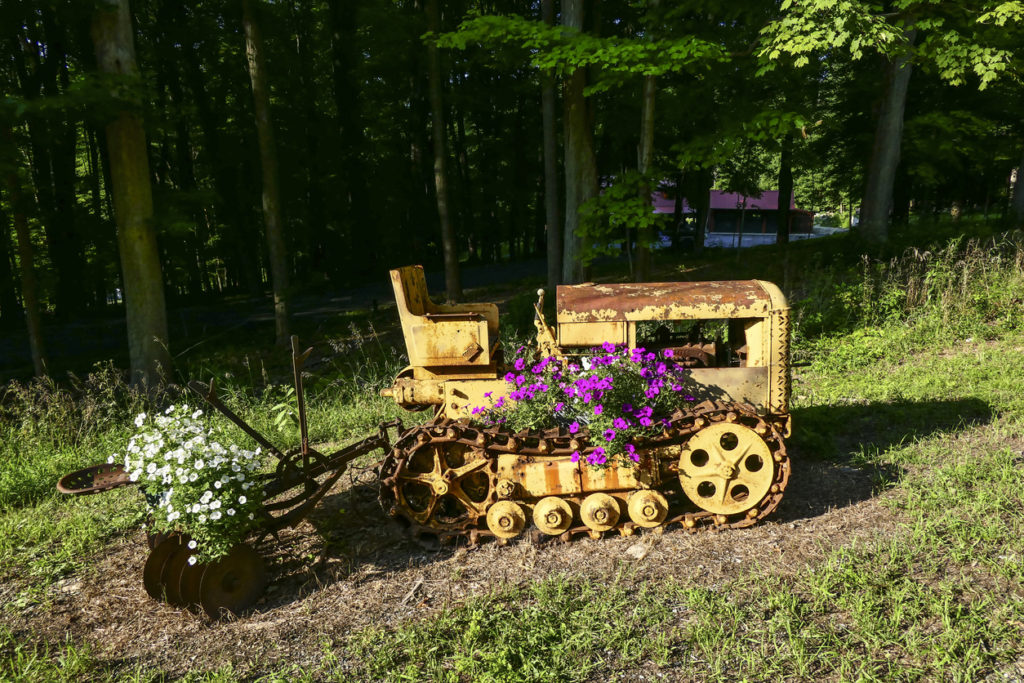 An old Caterpillar tractor repurposed into a flower pot on the side of the road. (Amenia, Dutchess County, New York, USA