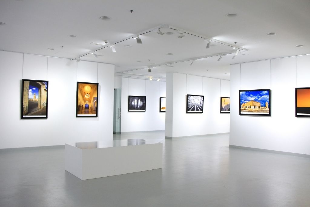 Modern art gallery with sleek, white walls and paintings for sale.