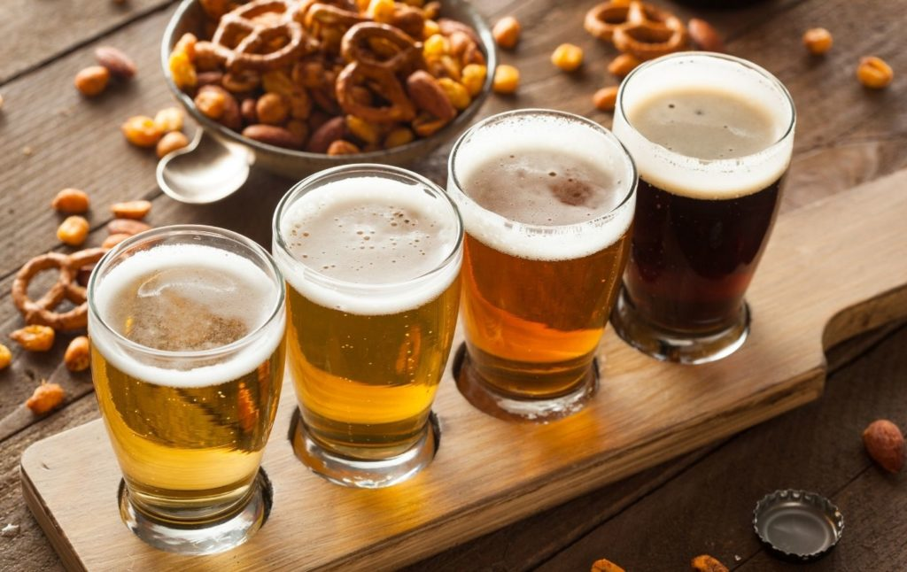 A tasting plate with four beers on it with peanuts and pretzels in the background.