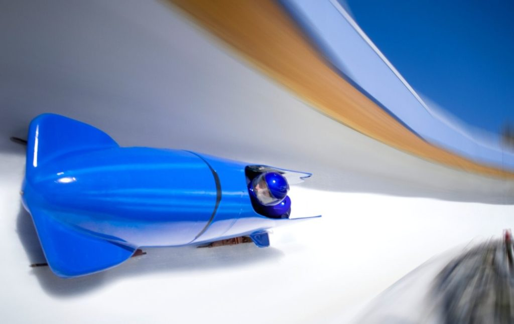 Bright blue bobsled sliding down the track with two passengers in blue helmets,