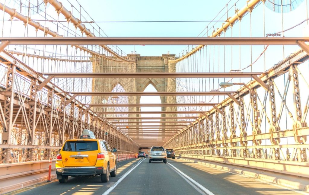 Cars and taxis driving across the Brooklyn Bridge in New York City. One of the many pros and cons of living in New York City is the traffic.