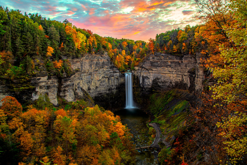 View of Taughannock Falls surrounded by fall foliage in New York, one of the best hikes in Upstate New York.