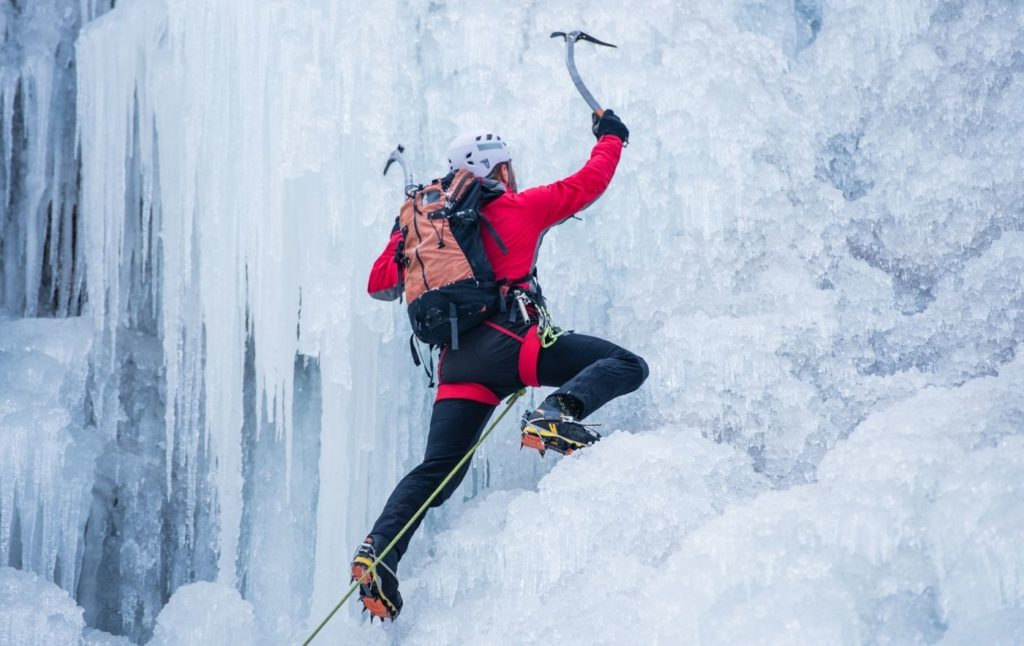 Climber in a red jacket going up an ice wall in Lake Placid.
