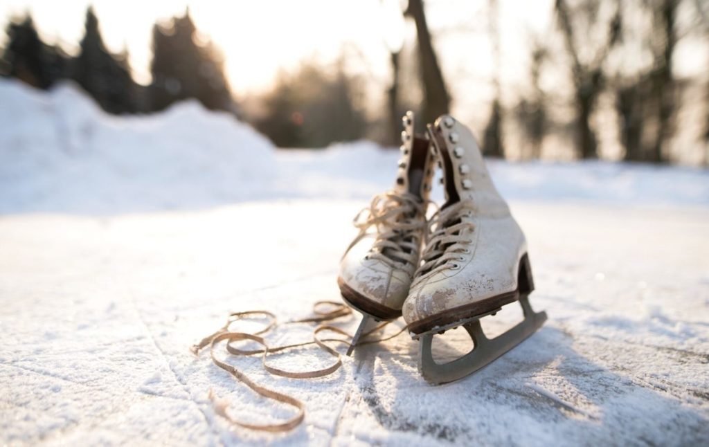 Old and dirty white figure skates on a frozen pond.