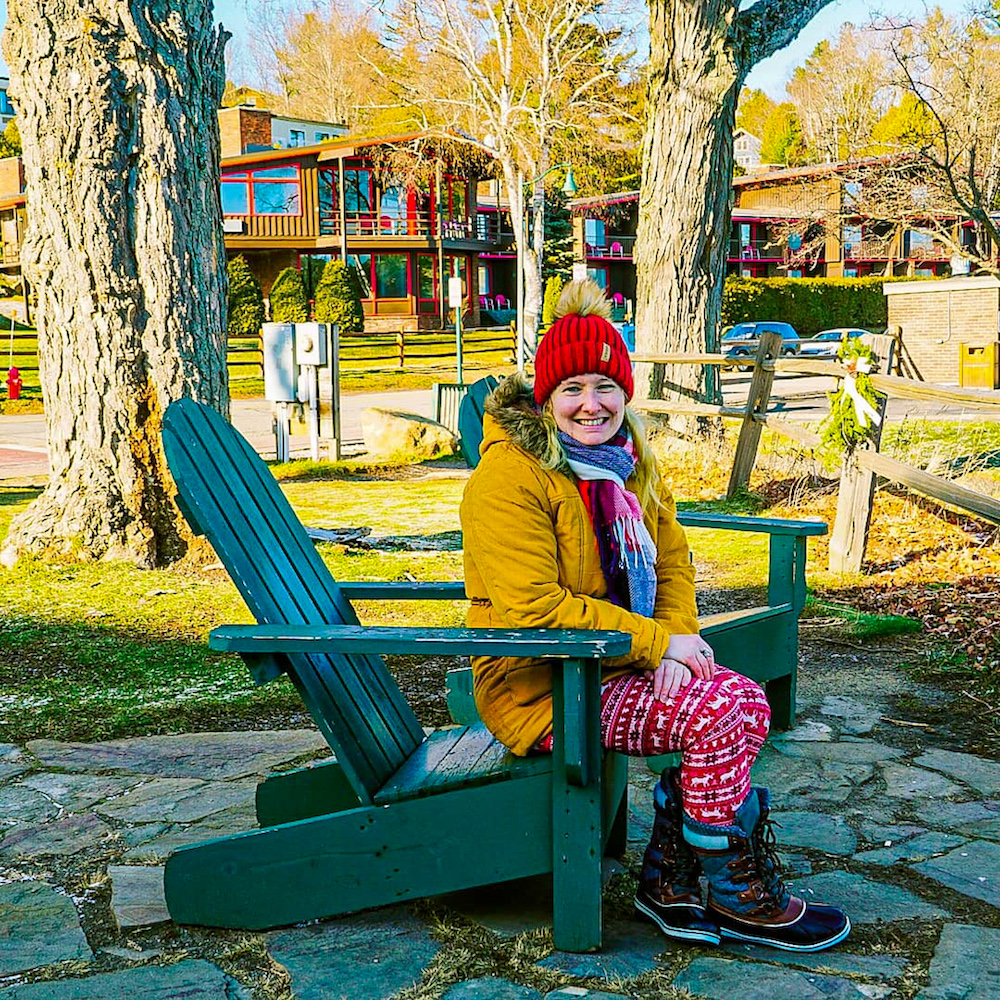 Woman sitting on a green Adirondack chair in winter in Lake Placid.