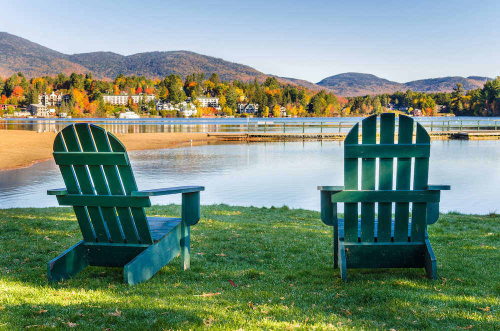 Two green Adirondack chairs in front of Mirror Lake in Lake Placid.