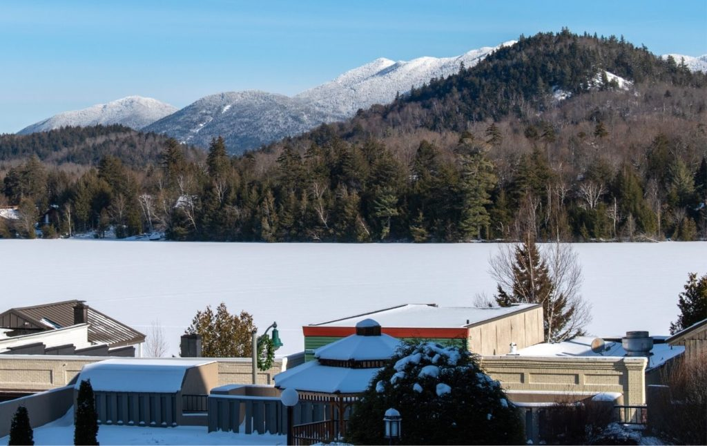 Lake Placid in winter with snow on the buildings and Mirror Lake frozen.