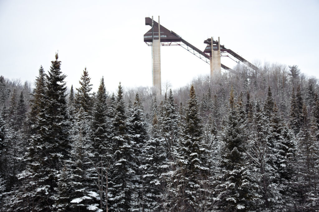 Lake Placid ski jumps surrounded by pine trees covered in snow.
