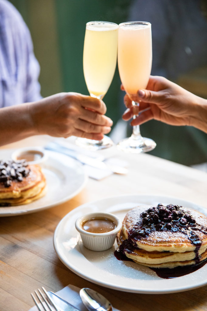 Mimosas and blueberry pancakes at Clinton Street Baking Company in NYC. Brunch is one of the pros on this list of pros and cons of living in New York City.