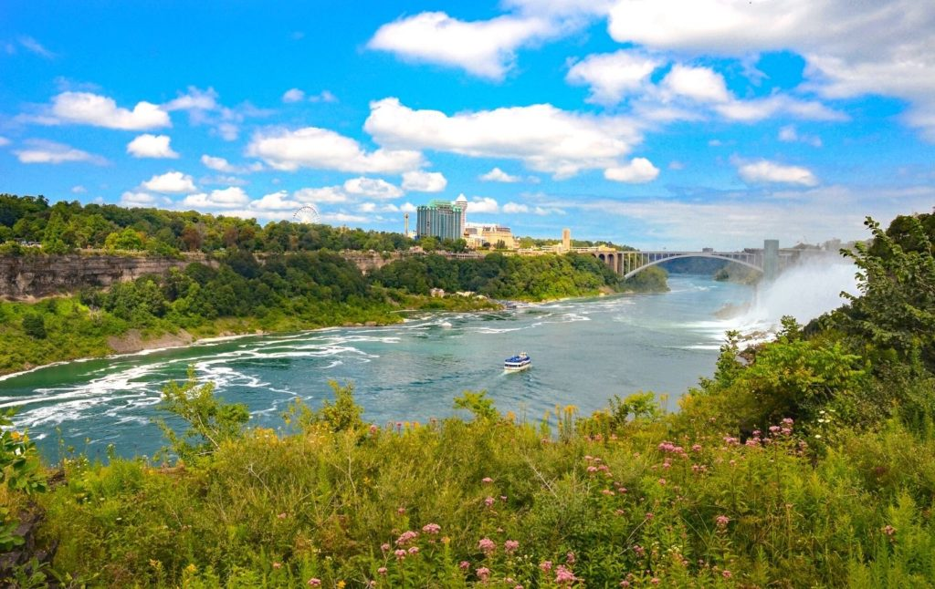 View of the Niagara River Gorge with a boat and the rainbow international bridge in the background.