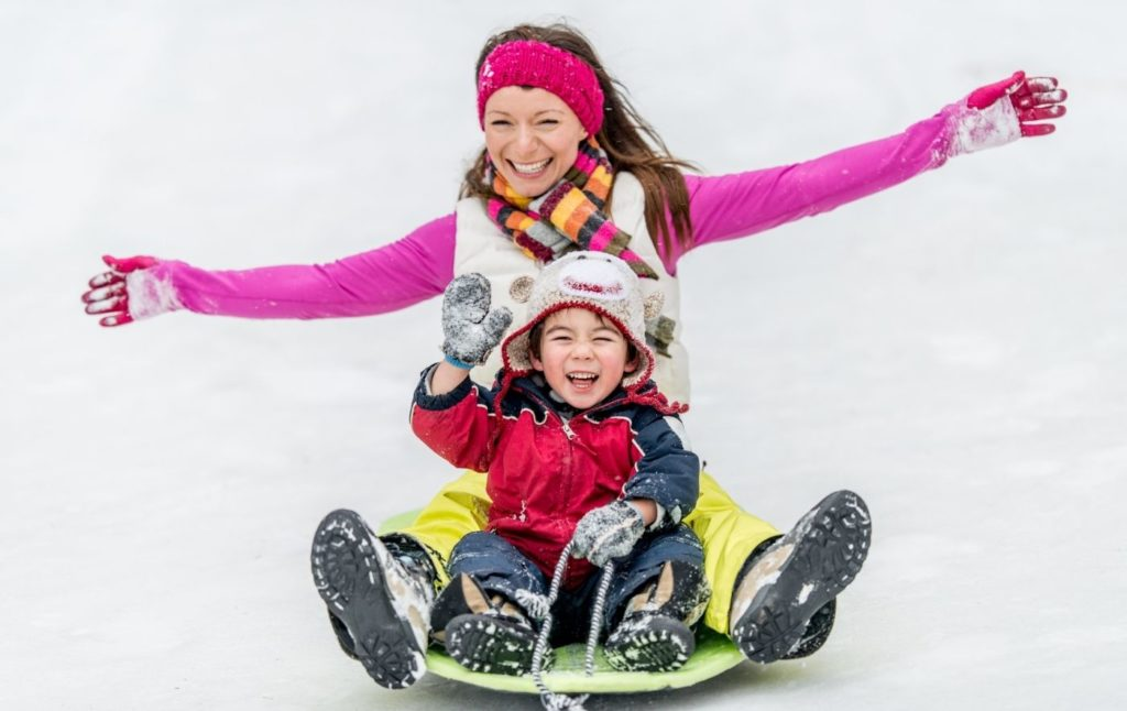 Mother and child sledding together in the winter.