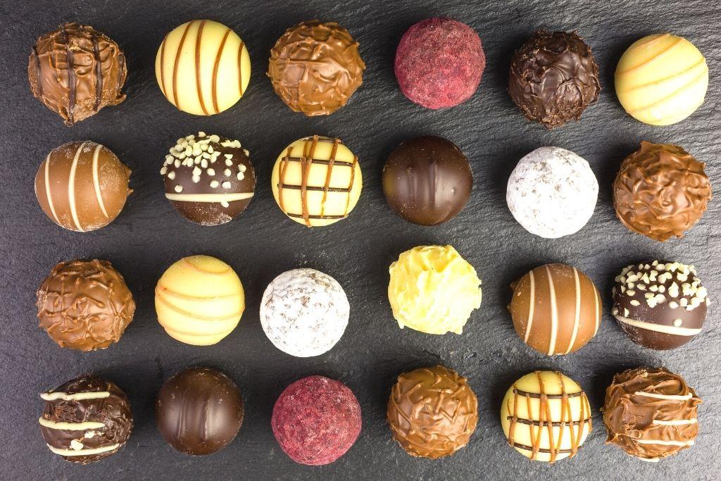 Homemade chocolate truffles on a granite counter.