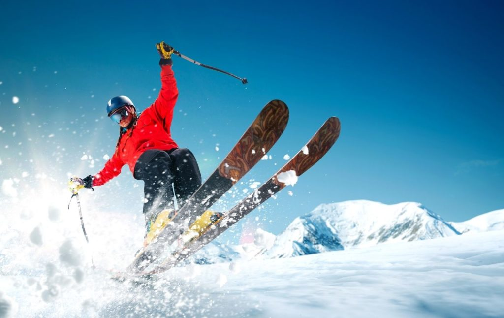 Skier in a red jacket cruising through the air and going down a snowy mountain.