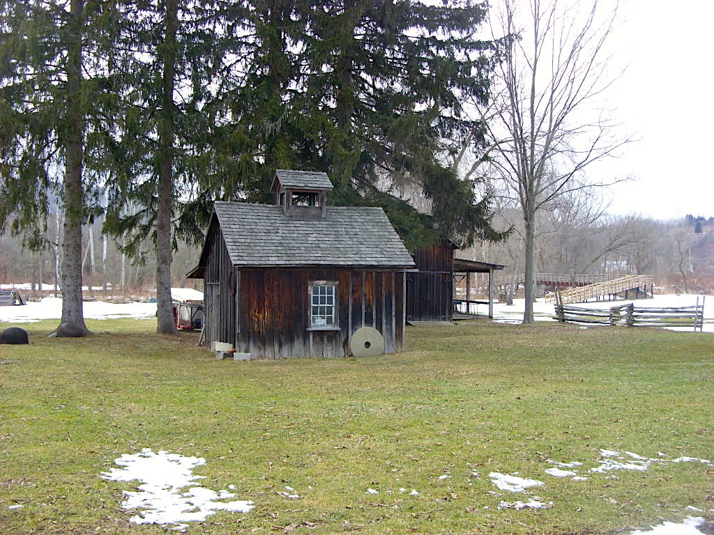 Historic wooden buildings with snow on the ground at the Bement-Billings Farmstead.