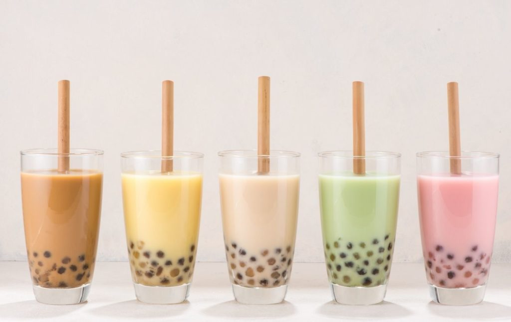 Five different bubble teas on a table in different colors.