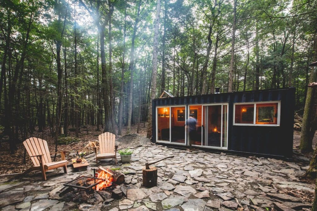 A black container cabin that is now a tiny house New York getaway with an outdoor fire pit and two Adirondack chairs.