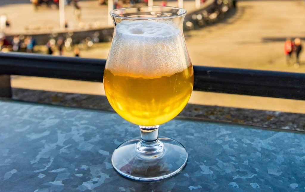 Light Belgian beer in a glass and on a table.
