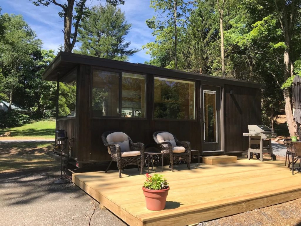 Mocha colored tiny house with a deck in the South Cairo, NY.