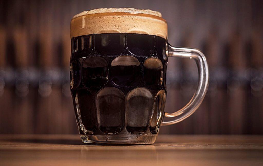 Mug full of extra dark beer on a table.
