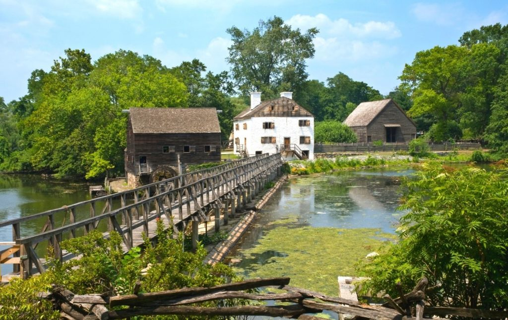 Ancient farm houses and walks ways on the water in Philipsburg Manor in New York.