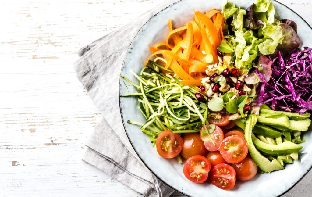 Salad in a bowl on a white, wooden table.