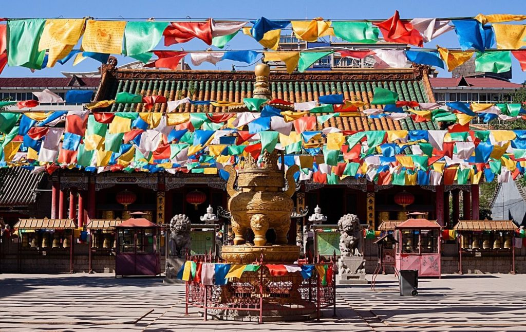 Tibetan Temple with vibrant prayer flags out front.