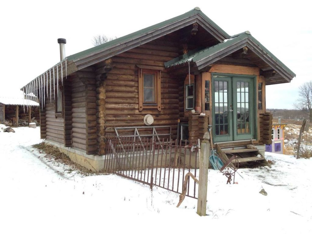 """Tiny house in """"Karenville"""" near Ithaca Ney York. It's covered in snow and is a log cabin with green doors."""