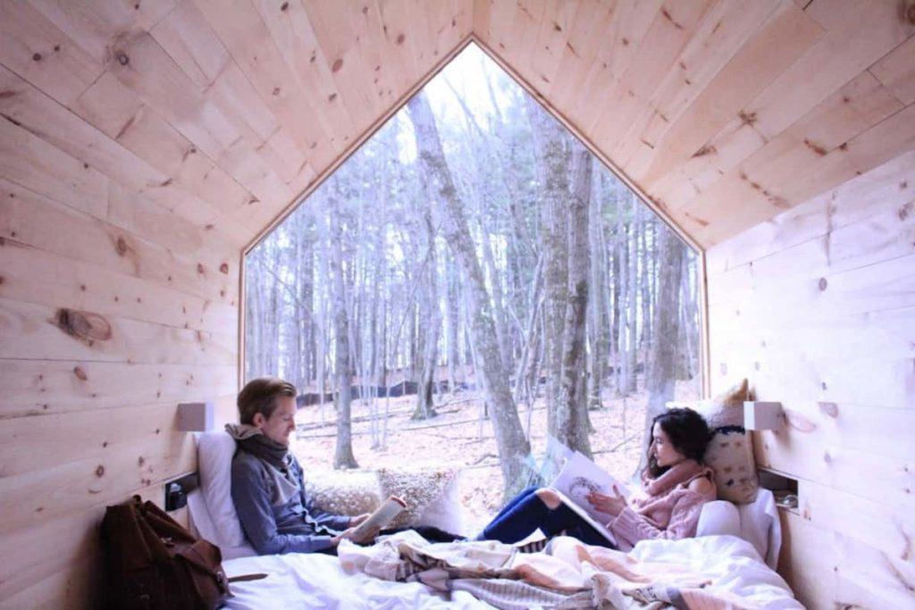 Couple reading while facing one another in bed of the tiny house cabin in Gable Green, New York.